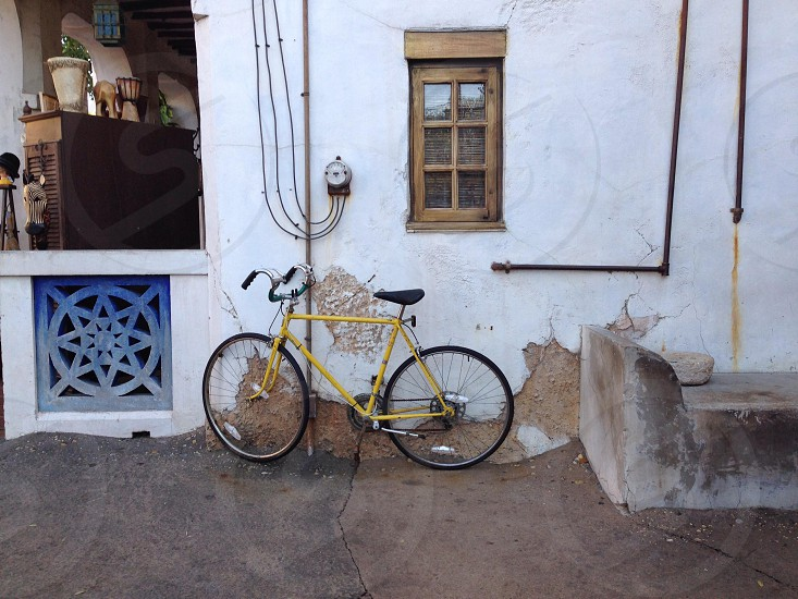 yellow and black bicycle a white concrete wall photo