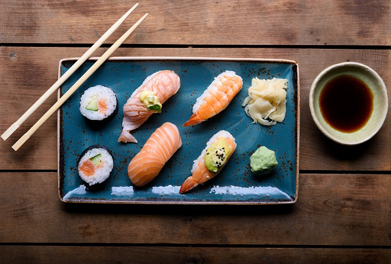 Blue plate with selection of sushi chopsticks and soy sauce on a vintage wooden chest photo