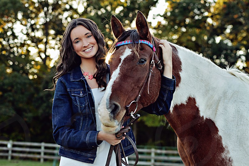 woman in blue denim jacket holding a white and brown horse photo