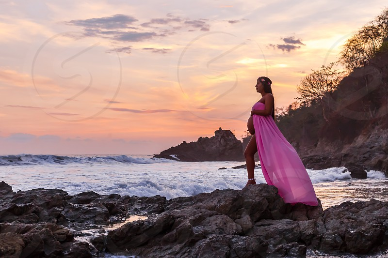 Shot of a pregnant woman in a pink maternity dress against a beautiful sunset over the ocean. photo