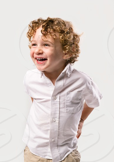 A 2 year old boy with curly blonde hair with a large happy smile on a white studio background. photo