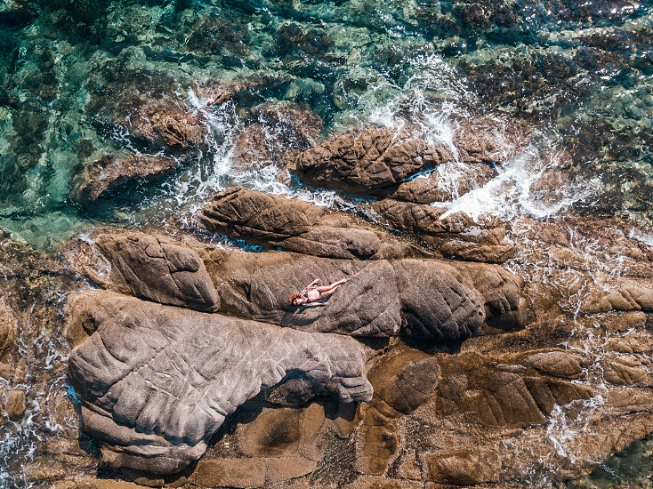 Aerial view of a woman sunbathing on the rocks near the sea photo
