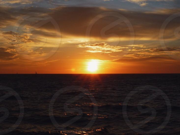 sun sitting down on ocean photo