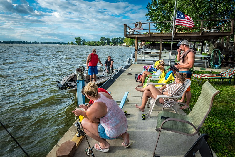 Group of people sitting on the dock relaxing at the lake fishing boating and sitting. photo