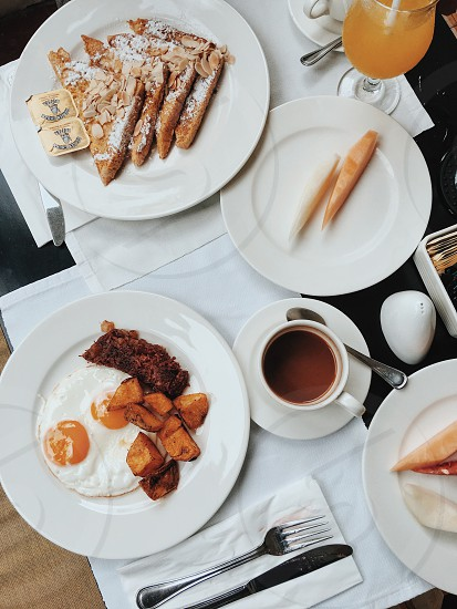 sunny side up with cooked meat beside other dishes on white ceramic plate photo