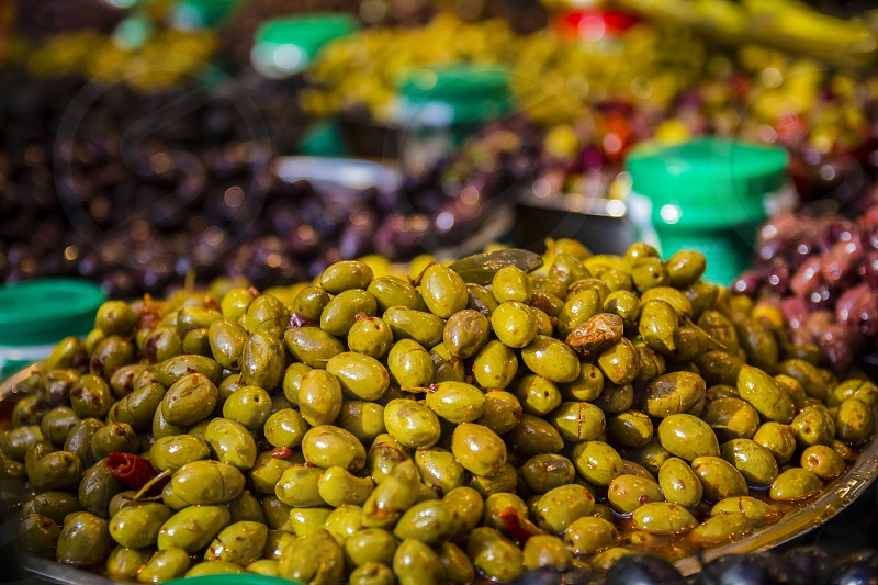 Olives at a market stall. A variety of types of olives. Green black Syrians and others.