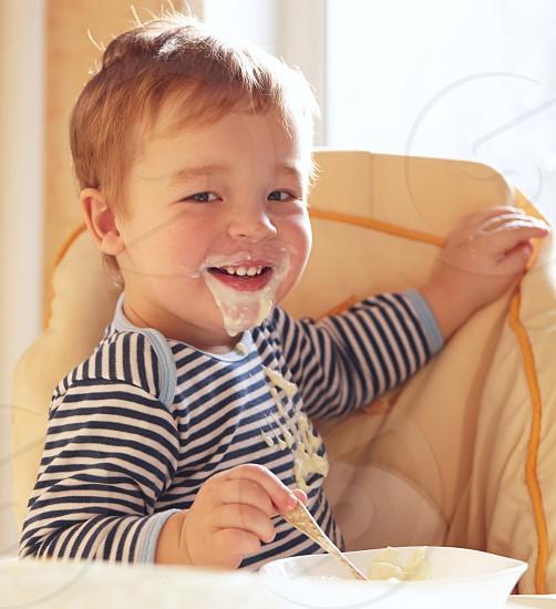 Two year old boy smiles to the camera eating porridge. photo
