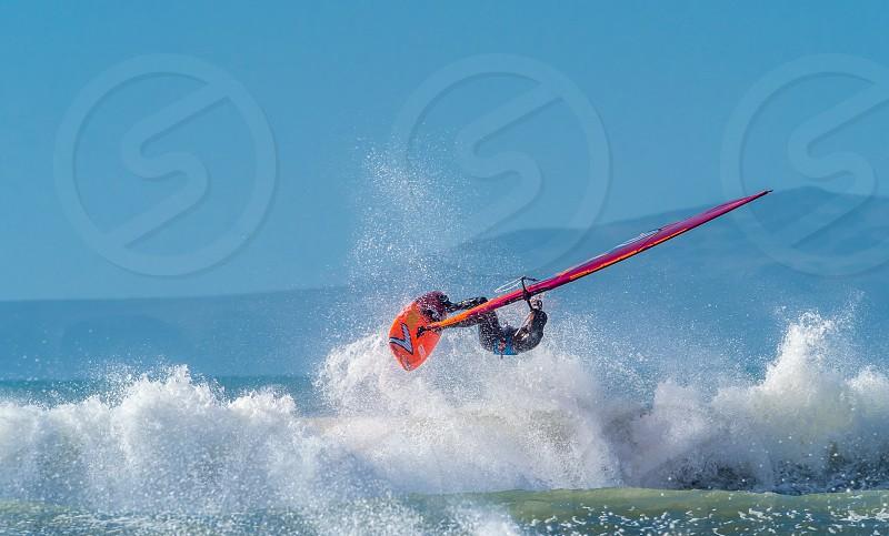 Windsurfing on Newgale Beach. A skilled windsurfer tackling the high waves on Newgale Beach Pembrokeshire. photo