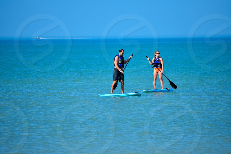 St. Pete Beach Florida. January 25 2019.  Couple enjoying stand up paddle board on blue sea background (1) photo