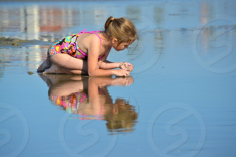 Young girl playing in shallow reflecting water on beach photo