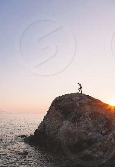 Brave man running over a rock near ocean in sunset photo