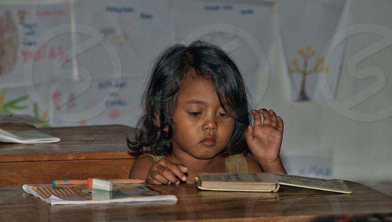 little poor girl in classroom reading a book photo