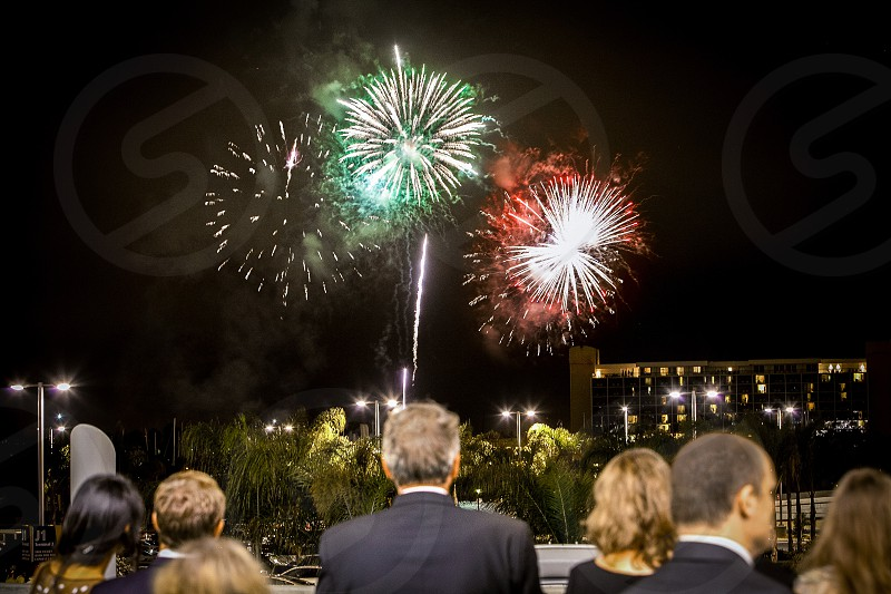 A group of party-goers celebrating by watching fireworks in the distance.  Explosion formal balcony hotel palm trees night event occasion. photo