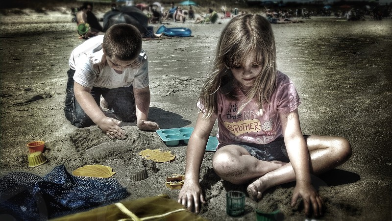 Kids playing in sand at beach.  photo
