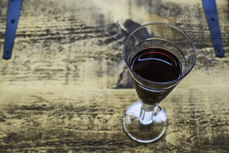 A Glass of red wine on a wooden table. photo