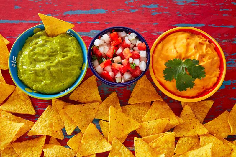 Mexican food nachos guacamole pico de gallo and dipping cheddar cheese photo