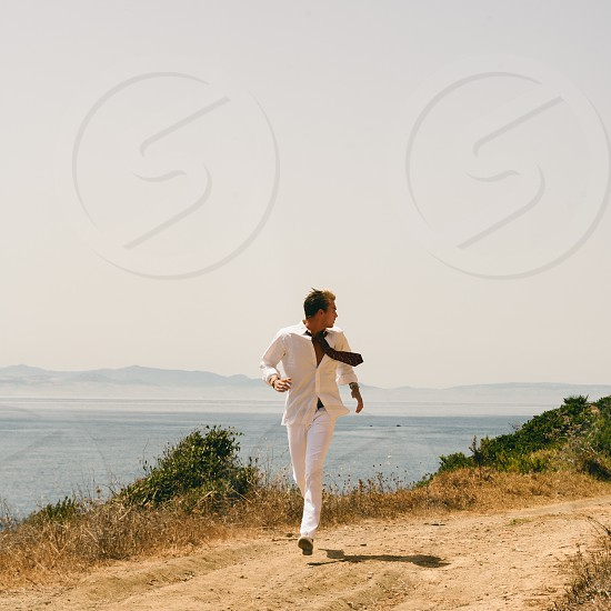Young Handsome Man Running at the Seaside. Full Length Shot of a Young Handsome Man Looking his Behind While Running on the Pathway at the Seaside. photo