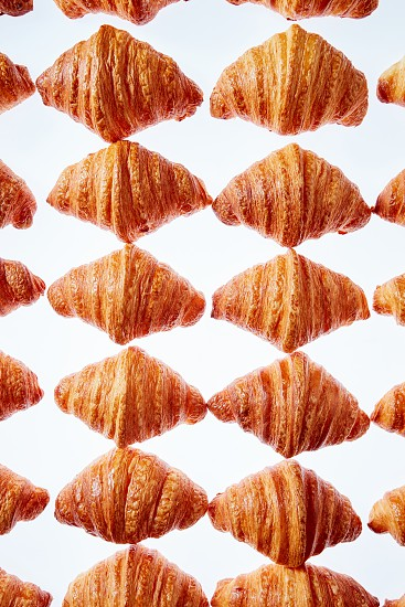 Freshly baked tasty french croissants as a hombus pattern on a light gray background. Continental breakfast concept. photo