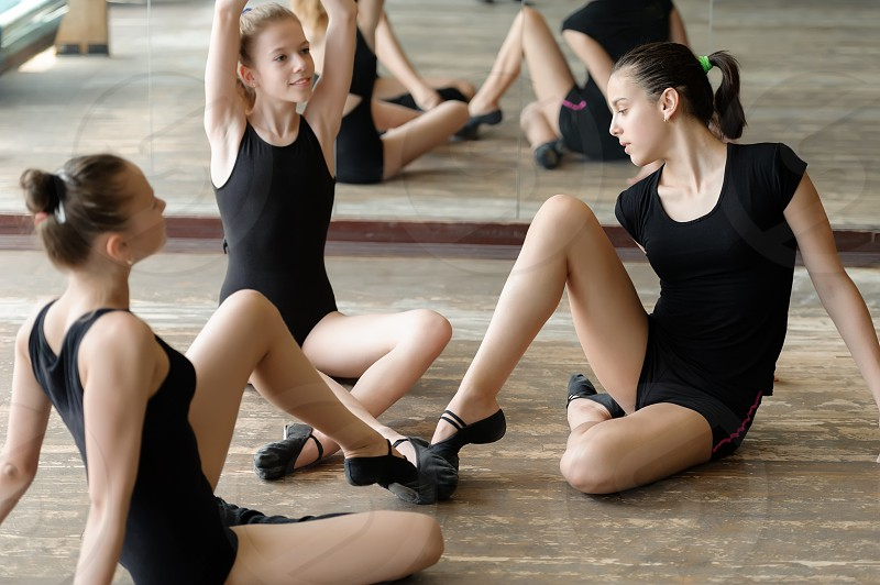 Three ballet dancers on the floor with their toes touching photo