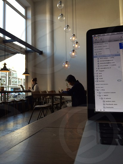 Working on a MacBookPro Apple computer in a coffee place in Rotterdam photo
