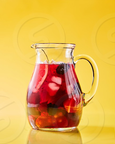 Freshly made berry fruit drink in a glass jug on a yellow background with copy space. Summer vitamin beverage photo