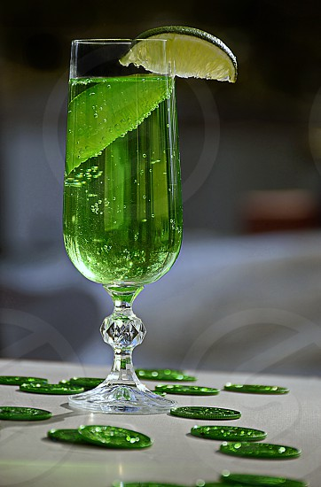 St Patrick's Day drink green beverage with lemon and lime. Fancy crystal glass. coins on the tabletop photo