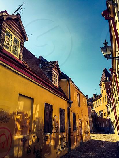 Outdoor day horizontal colour colourful filter haze yellow blue mustard alley alleyway street road cobble cobblestone tradition culture medieval town Tallinn Estonia Europe European travel tourism tourist photo