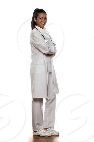 full length of a young woman doctor with arms folded photo