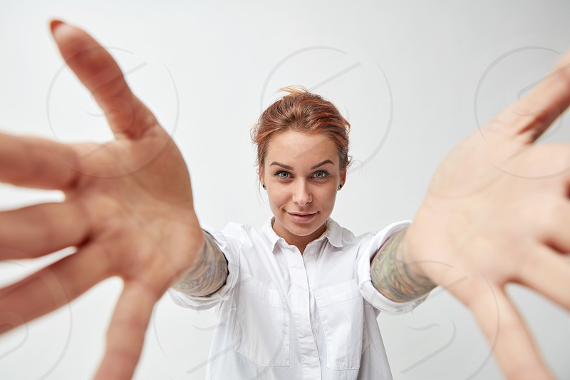 Cute red-haired woman with open arms. Gesture of welcome photo