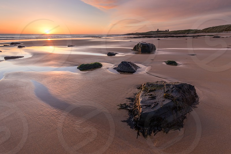 Dunstanburgh Castle at dawn. The 14th century castle is one of several built along the Northumberland Coast to defend against attack. photo