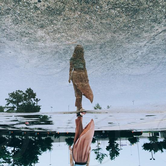 woman wearing pink skirt standing near body of water photo