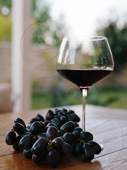 wine glass beside grapes on top of table photo