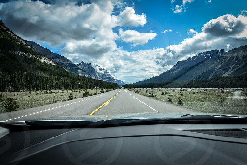 Driving down a Canadian road surrounded by mountains and trees.  photo