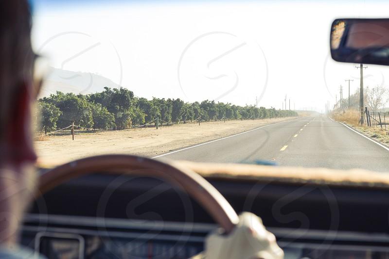 man wearing black tinted sunglasses holding brown steering wheel photo