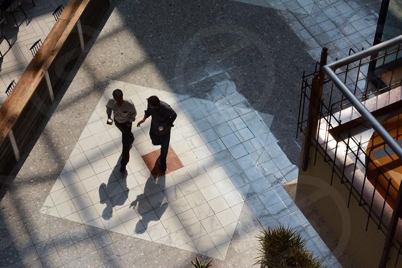 two people walking on the sidewalk photo
