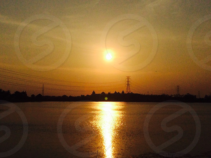 Sunset over the high-voltage lines with lakeside scene photo