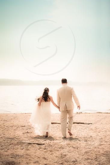 Wedding Marriage Groom Bride Beach Barefoot Sand Love Sky Landscape Water Lake River Vow Hands Holding Bouquet Tuxedo Dress Brunette photo