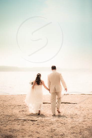 wedding marriage couple bride groom beach water lake river matrimony sand barefoot love holding hands tuxedo dress bouquet  photo