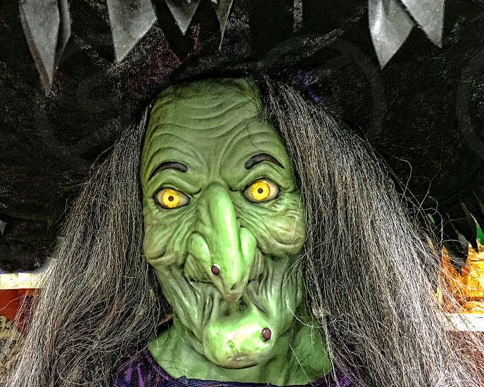 Scary mask of a Halloween green faced witch photo