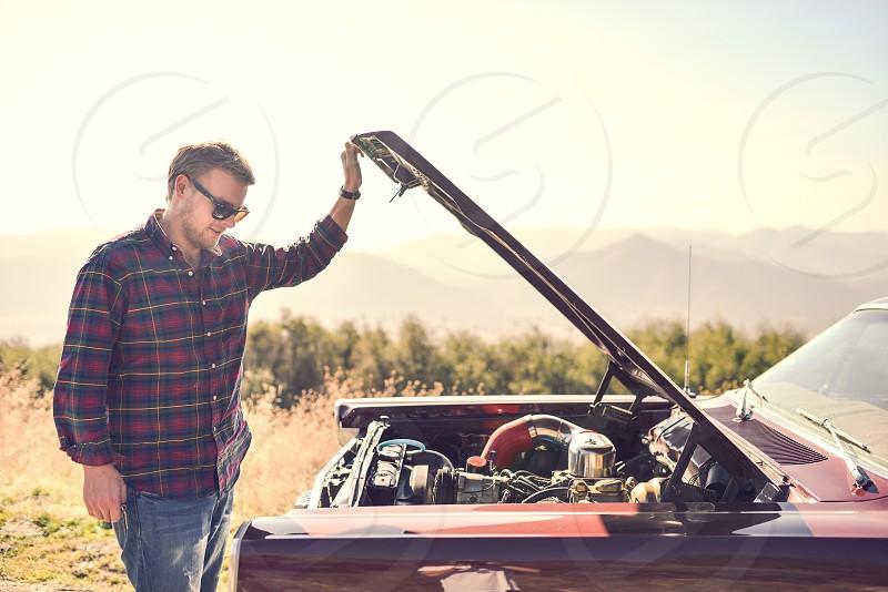 man looking at car engine photo