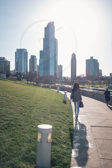 woman walking on concrete pavement near on garden bollards and green grass yard in front of a high rise buildings photo