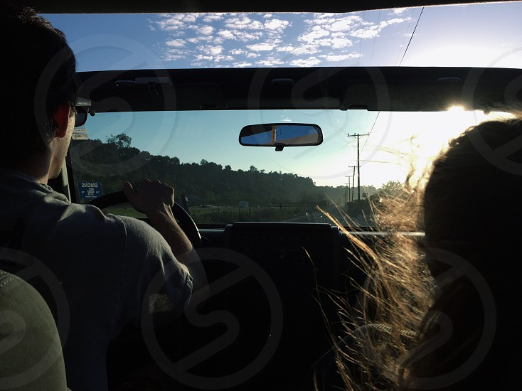photography of man driving vehicle beside woman during daytime photo