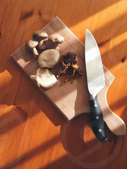 mushroom on brown wooden chopping board beside black handled knife on brown wooden table photo