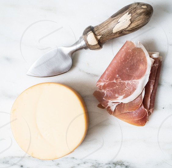A cheese board with prosciutto and gouda on a piece of white marble.  photo