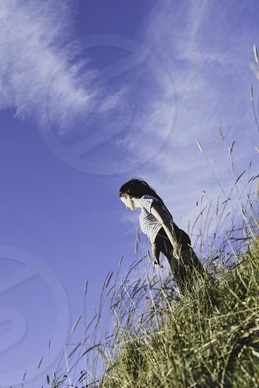 Teenage girl walking on hillside. photo