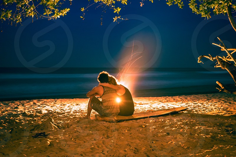 A couple embraces one another while watching the flames dance and the waves crash on a beautiful deserted beach in Nicaragua. photo