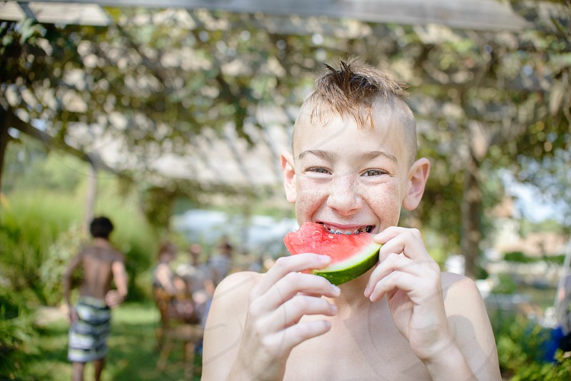 boy eating sliced watermelon during daytime photo
