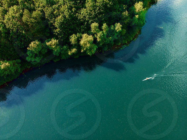 Wonderful aerial shot of man swimming in kayak on blue river water. Drone view. Floating alone on the lake in canoe. Sports activity adventure concept. photo