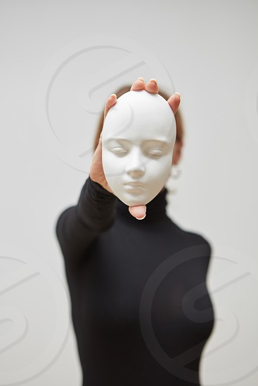 Girl in a black jumper hold gypsum mask sculpture instead of face on a white background place for text. Concept The masks we wear. photo