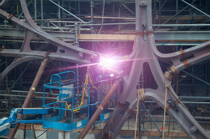 Welder works from a raised platform at a construction site. photo